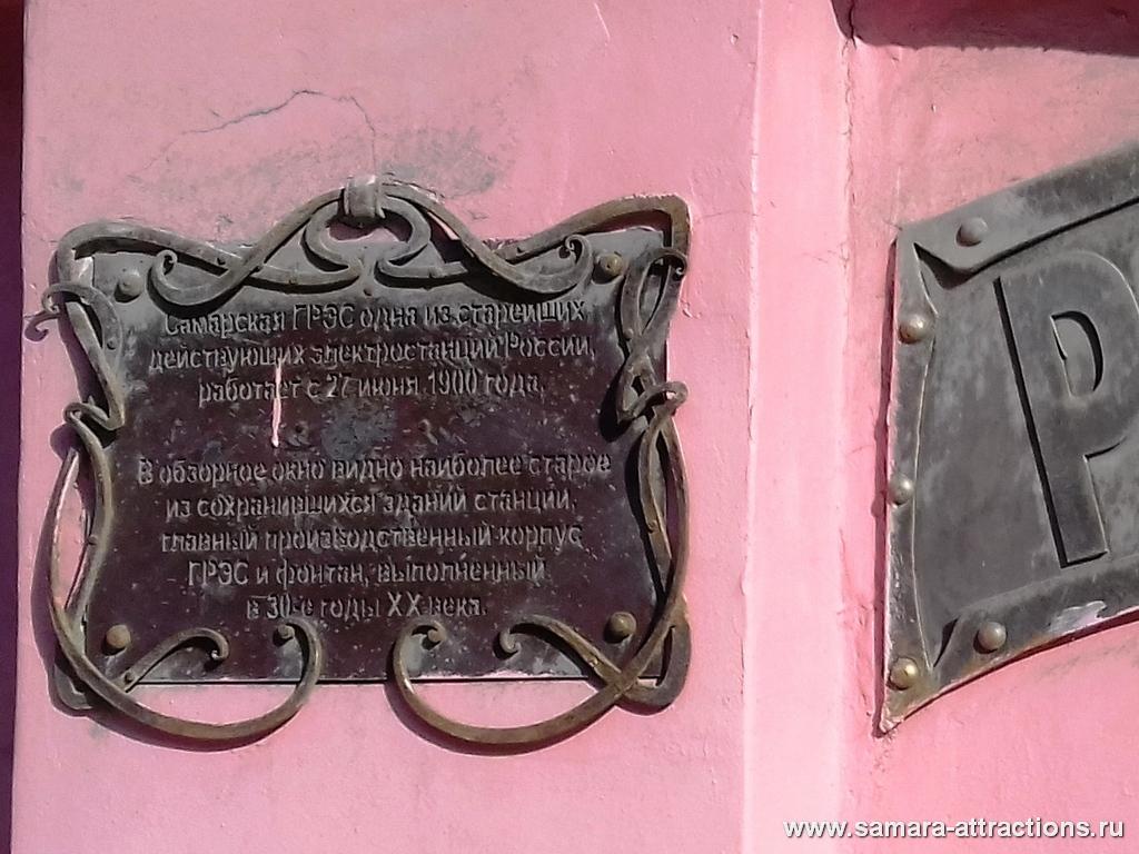 Памятная табличка на заборе рядом с декоративным окном